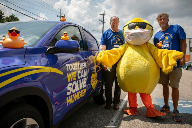 Mark Bodnar, the current chair of the Rubber Duck Regatta steering committee and Mick Clay, the Freestore's director of development operations, stand with 'Quacky' at the Freestore Foodbank on Aug. 18, 2021.