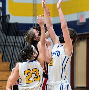 Players are seen wearing face masks in an Oconto girls basketball game from February, in which a Sevastopol player tries to get a shot off over defenders Lauryn Hendzel and Hannah Moe.