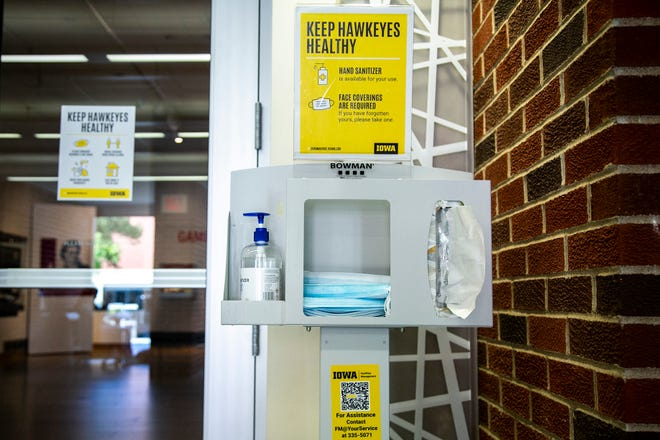 A station with hand sanitizer and face masks is seen on the first day of the fall semester, Monday, Aug. 23, 2021, at the University of Iowa Main Library in Iowa City, Iowa.