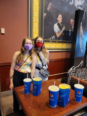 Wendy and Alex Schwabe get ready to watch a movie at a theater for the first time since the pandemic started.