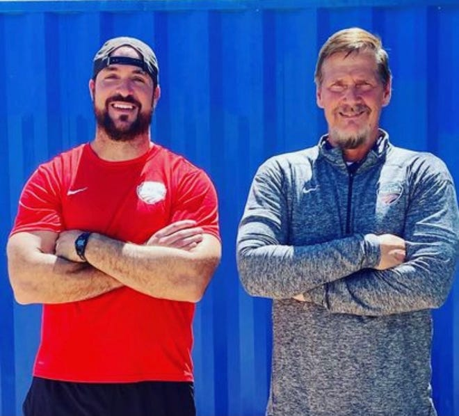 Larry Judge (right) stands with one of his athletes, Jeremy Campbell (left).