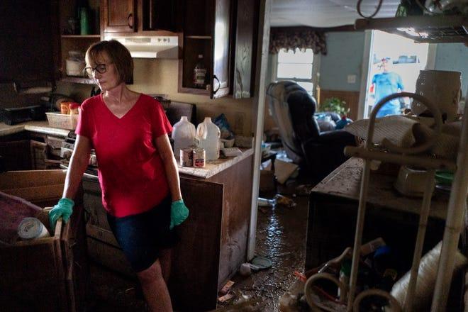 تعمل جاكيتا بوكانان على إنقاذ الأشياء من منزل والدتها في ويفرلي ، بولاية تينيسي ، الاثنين 23 أغسطس ، 2021. هربت والدتها من المنزل بأمان ، لكن والدها توفي أثناء مساعدة أحد الجيران.  ضرب ما يصل إلى 17 بوصة من الأمطار مقاطعة همفريز يوم السبت ، مما تسبب في ارتفاع منسوب مياه الفيضانات في جميع أنحاء المنطقة مما أسفر عن مقتل العشرات.
