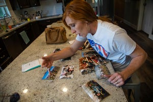 Jennie Taylor, looks through printed pictures of her husband Maj. Brent Taylor and his time in Afghanistan in her North Ogden, Utah home.