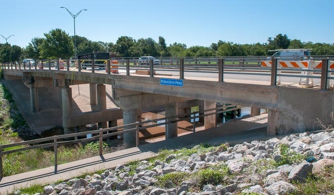 Construction workers worked to finish repairs on the north lane of the Midwestern Parkway Bridge Monday morning.