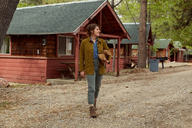"""Lindsey Kurowski poses in front of cabins at the Oak Knoll Lodge, a property in Big Bear Lake, California that she restores for """"Inn the Works,"""" streaming on the Magnolia and Discovery+ apps."""