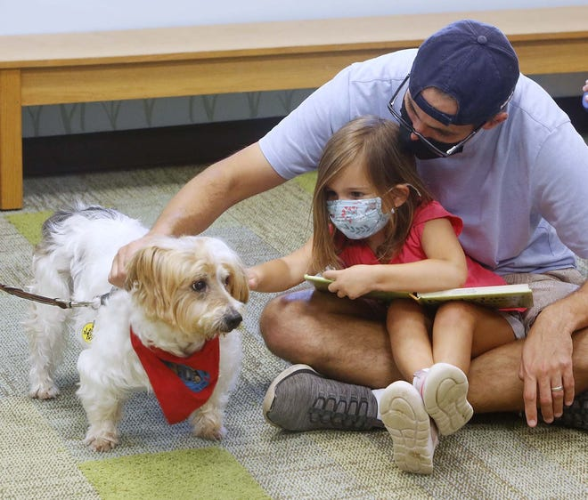 Tony Dockus, right, and his daughter Nora, 4, pet Eddie during Paws to Read at the Twinsburg Public Library on Aug. 21. The next Paws to Read program at the library is scheduled for  Sept. 11 from 11 a.m. to 12:30 p.m.