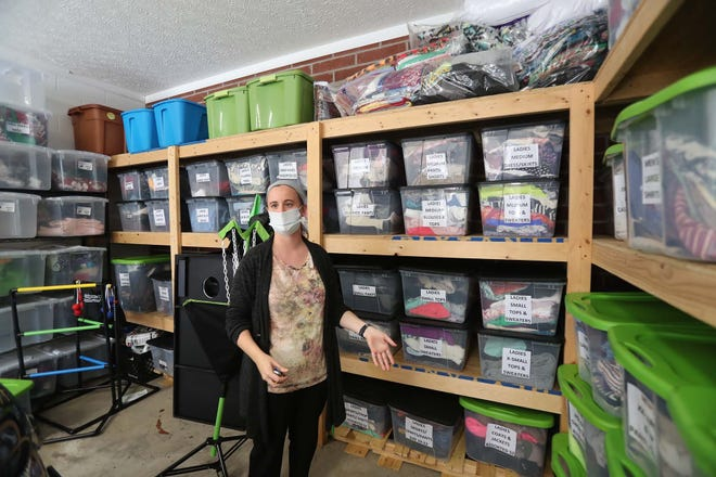 """Jessica Purdy, a case manager with Street Outreach Services, stands in front of the agency's supply of donated clothing and houseware items for youth seeking their assistance. """"Some of the young adults, especially if they've been on the street, they may not have an extra pair of shorts,"""" Purdy said."""