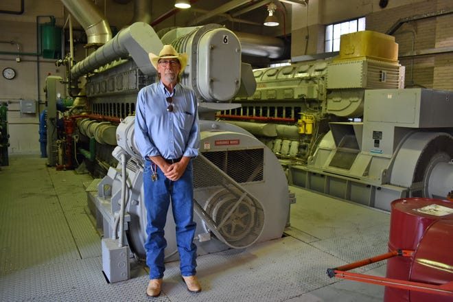 Jeff Ishmael, Story City Municipal Electric Utility administrator, poses next to Engine 6 at the plant. Ishmael is retiring Aug. 31 after 24 years with the utility.