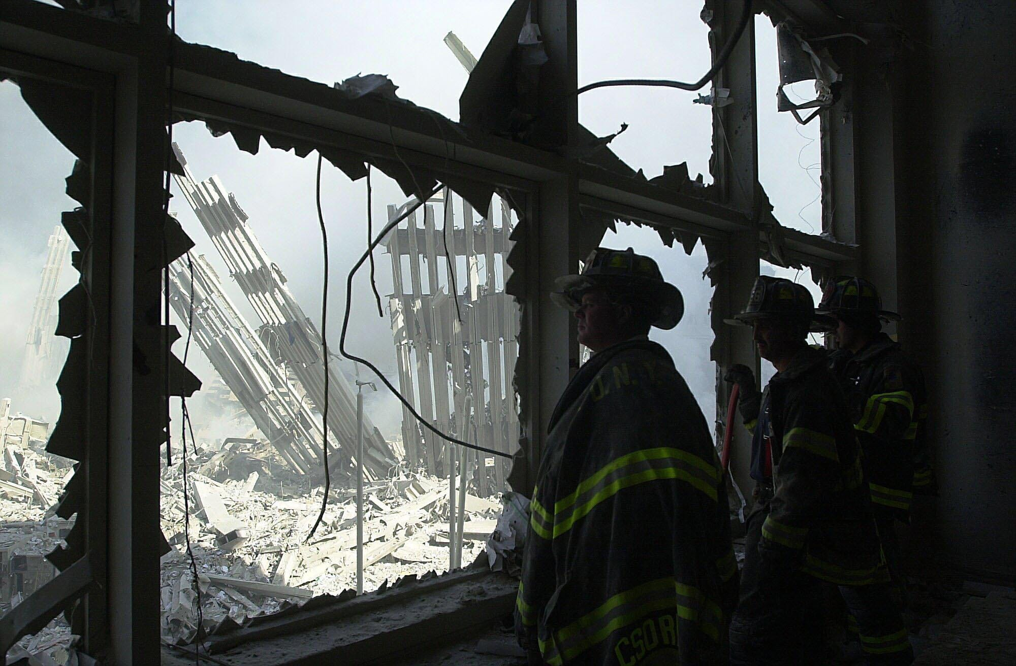 New York City Firefighters look at the remains of the World Trade Center on Sept. 11, 2001.