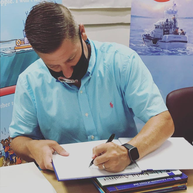 United States Coast Guard Chief and children's author Tyler Benson returned to the Cheboygan Area Public Library Saturday and read one of his books to fans. He also signed a number of books and answered questions.