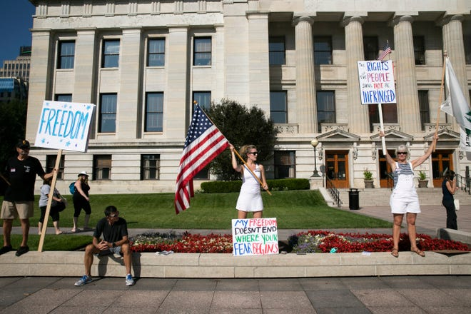 """Protesters line the west side of 3rd Street in front of the Ohio Statehouse in Columbus, Ohio on August 24, 2021. People gathered to support or protest House Bill 248, """"the Vaccine Choice and Anti-Discrimination Act,"""" which lawmakers were debating inside."""