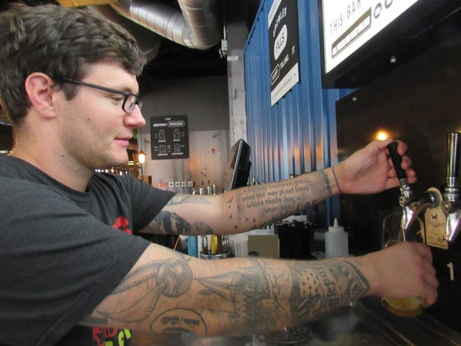 Duty manager Donoven Browning pours a pint of Elvis Juice at the new BrewDog taproom at 97 E. Dublin-Granville Road in New Albany's Village Center. Elvis Juice is one of the classics at BrewDog, whose USA headquarters is in Canal Winchester.