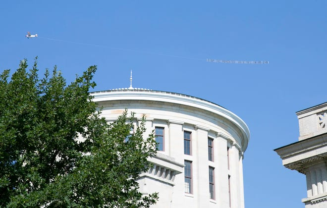 """Ohio lawmakers have introduced a bevy of bills to block requirements for vaccines and other COVID-19 mitigation measures. A plane pulling a sign that reads """"Stop the mandates vote yes on HB 248"""" flies over the Ohio Statehouse in Columbus, Ohio on August 24, 2021."""