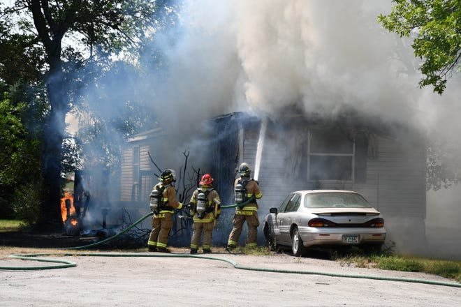 Firefighters work to put out the flames