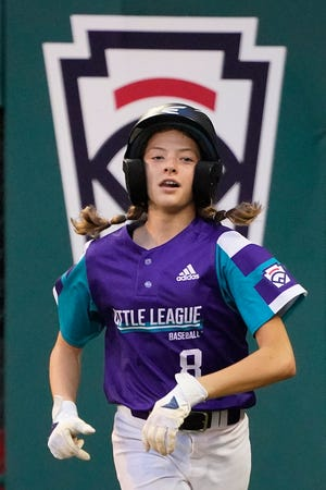 Abilene, Texas' Ella Bruning runs back to the dugout after scoring on a wild pitch by Sammamish, Wash., starting pitcher Sanath Chari during the second inning of a baseball game at the Little League World Series in South Williamsport, Pa., Friday, Aug. 20, 2021. (AP Photo/Gene J. Puskar)