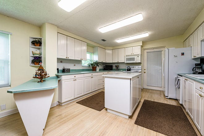 The light cabinets and flooring in this open kitchen make it bright and cheerful, just like the rest of this super-spacious home.