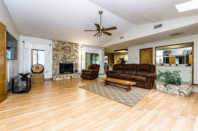 Bright and open, with high ceilings, this large living room boasts a gorgeous stone fireplace, a built-in bar area and sliding doors that open to the screened patio, with a private in-ground spa.