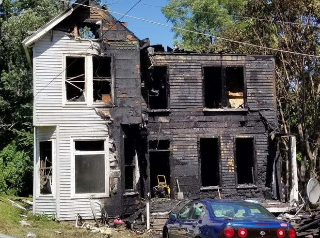 Fire crews investigate the aftermath of a fire in an apartment building at 1126 Washington St. in Burlington on Tuesday, August 24, 2021.