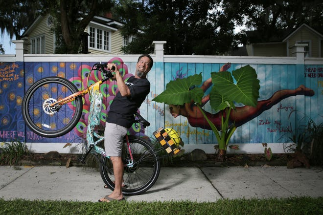 Ron Rothberg started Art Bikes Jax so people could experience the city's public art. The company rents electric bikes such as this one, customized by Jacksonville artist Shaun Thurston. The mural is on the fence outside his Avondale home.