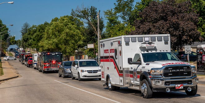 An ambulance carrying fallen paramedic Kyle Martincic heads down Second Street past IU Health Bloomington Hospital during a procession on Tuesday. Martincic, who also worked for IU Health Bloomington Hospital's Lifeline ambulance service, died Monday while on an emergency run for the White River Township Fire Department in Johnson County.
