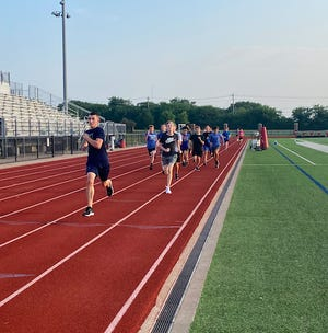 Heritage boys' cross-country runners get in some speed work during preseason practice on the HHS track.