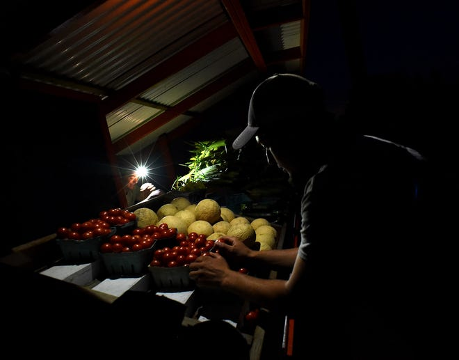 Tye Thompson (left) uses his headlamp to light up one of his produce stands. He is aided by best friend Brent Sieler. Thompson, a farmer from Dundee, owns and operates several produce stands in Monroe County.