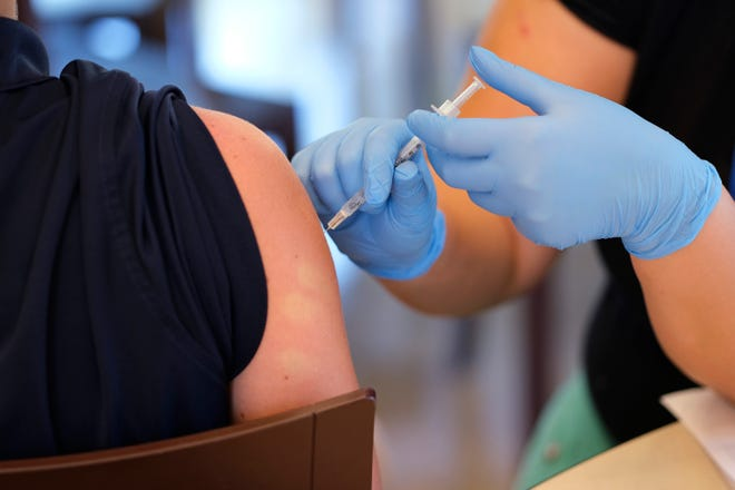 A health care worker gives a vaccination to a student at Mt. St. Mary's, where the Oklahoma City/Oklahoma County Health Department had a mobile vaccination clinic after school Monday, August 23, 2021.