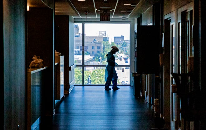 A nurse prepares to enter a room recently at SSM Health St. Anthony Hospital's COVID ICU to administer treatment to a patient.