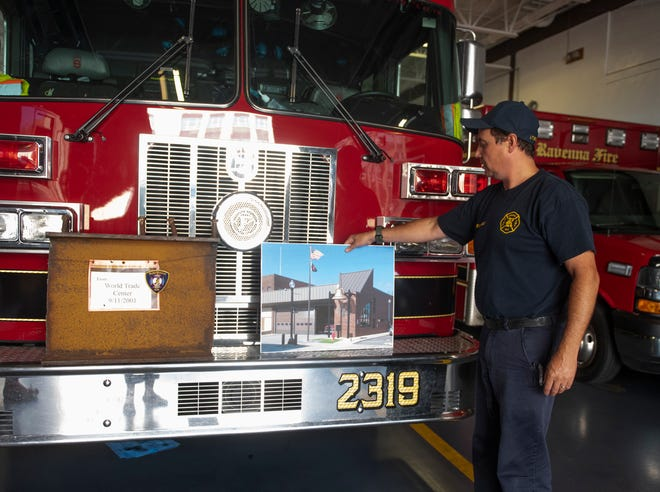 Ravenna City fire department plans on a permanent memorial for a September 11 beam. Lt. Chris Singleton places an architecture rendering of the memorial next to the beam on a Ravenna fire truck.