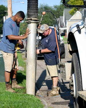 Triston Lalli, left, and Joe Henderson, utility servicemen with Alliance Water Department inspect water lines on W. Harrison Street for lead pipes as they work toward replacement.
