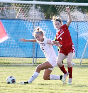 Martinsville senior Holli Reuter battles Bloomington North's Izzy Himebaugh (6) for the ball during Monday's game.