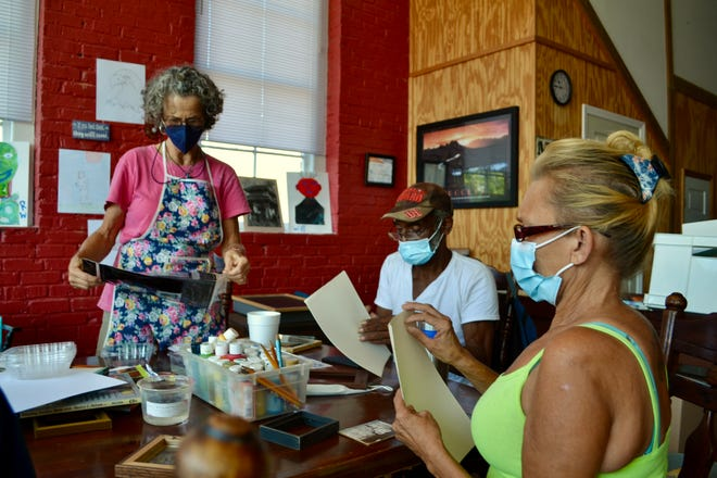 Terry McCullum leads an art therapy exercise with Sandra Warlick and Lawrence Wilson, two homeless people living in the city of Shelby.