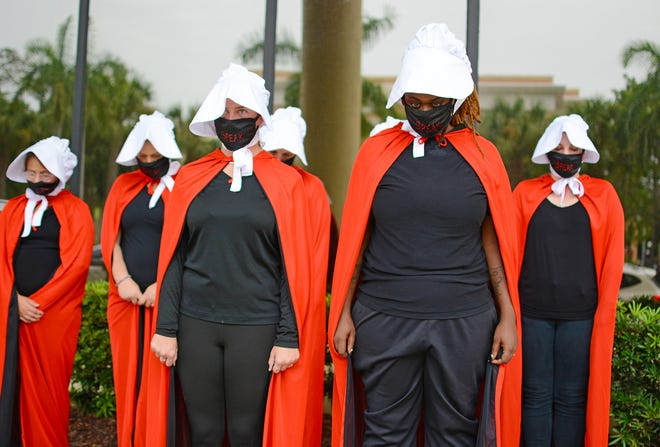 Abortion rights supporters dressed as handmaidens hold a peaceful demonstration at a Manatee County Commission meeting in August. They denounced the commission's discussion of a possible ban on abortion clinics.