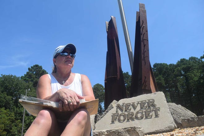 Lynn Pollak sits at the Fairfield Harbour 9/11 Memorial with her scrapbook, which includes photos she took at Ground Zero