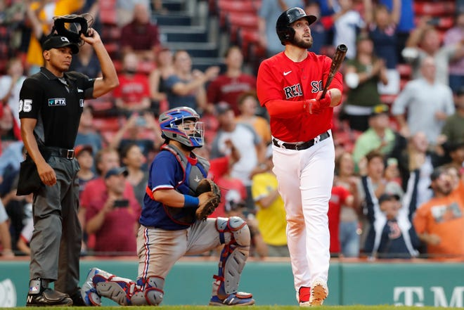 Boston Red Sox's Travis Shaw, right, watches his walk-off grand slam in front of Texas Rangers' Jose Trevino during the Red Sox's 8-4 Monday at Fenway Park .