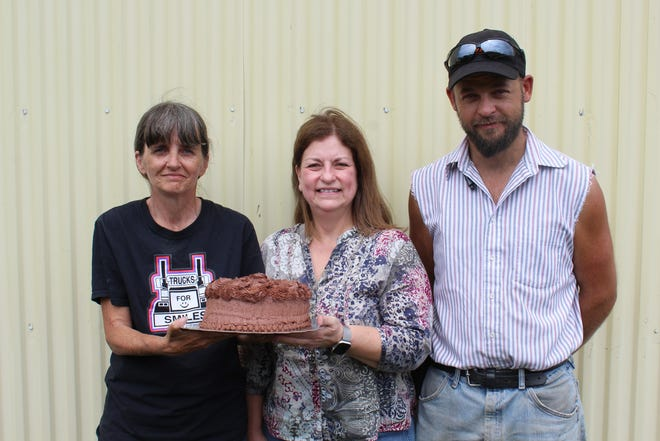 Betty Abbott (left) of Confluence bought the winning Pennsylvania Preferred chocolate cake for $400 during the baked goods auction at the Somerset County Fair on Sunday afternoon. Jill Fox (center) of Rockwood baked the first-place cake. C.J. Livengood (right), 34, a local maple producer who is taking dialysis for renal failure, was the beneficiary for the sale that raised more than $12,000.