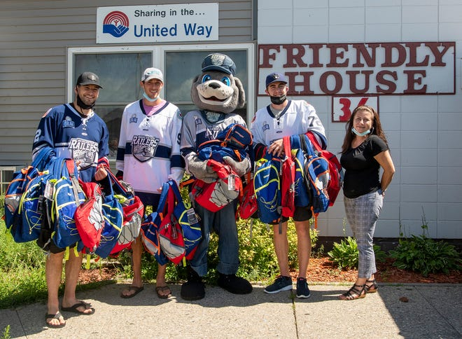 Worcester Railers players Jordan LaVallee Smotherman, Ross Olsson, mascot Trax, and Drew Callin deliver backpacks filled with school supplies to Friendly House's Susan Daly on Tuesday. Daly is the assistant to the executive director.