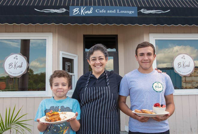 Ericka LaBonte, who owns B. Kind Cafe and Lounge in Webster, with her sons, Lucian, left, holding her vegan lasagna, and David holding her French toast with fruit.