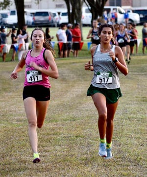 WHS sophomore Emilee Jones (right) runs to the finish line at the Waxahachie Woodhouse Invitational on Friday. Jones posted a personal best of 18 minutes, 8.2 seconds to finish fourth among individual runners.