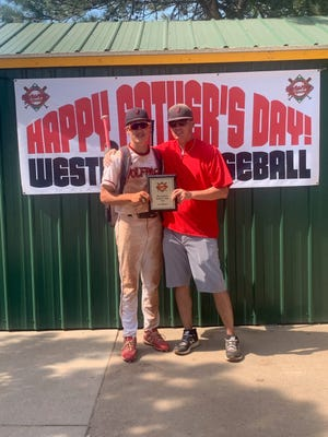 Sky Branam (left) with his father, Roy (right), holding a tournament plaque