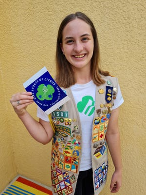 Girl Scout Marie Young with her Making Space for Girls patch design submission.  A printout of her design will fly to the space station on SpaceX's CRS-23 resupply mission.