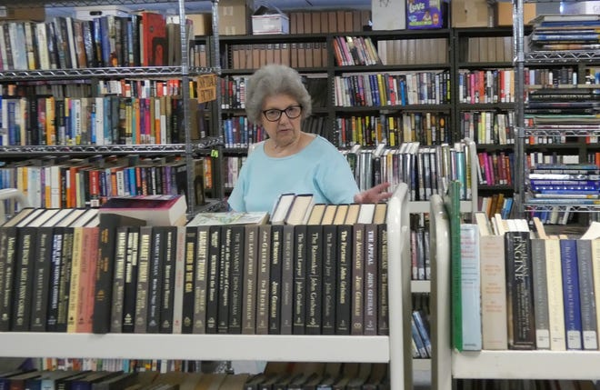 Roberta Siniff, vice-president of theFriends of the Bucyrus Public Library, examines a rack of books Tuesday as members prepare for this weekend's sale.