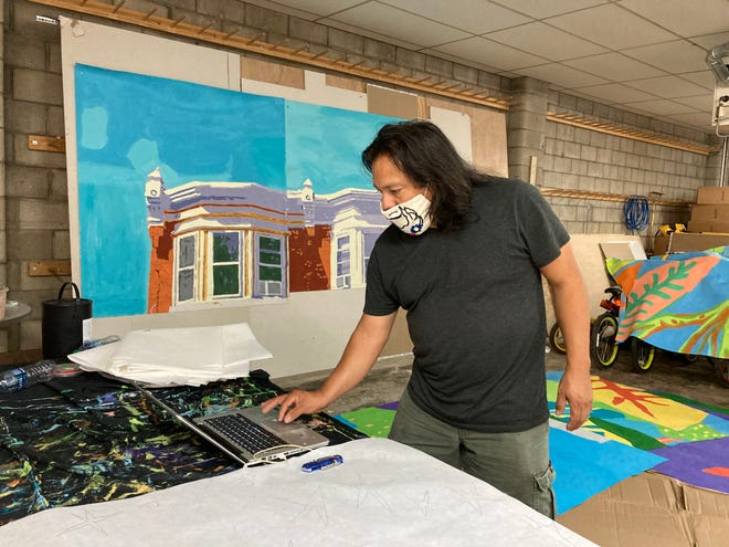 Artist Cesar Viveros checks a digital rendering of the mural planned for 27th Street and Westfield Avenue in Camden. Behind him are some of the panels in progress or awaiting assembly.