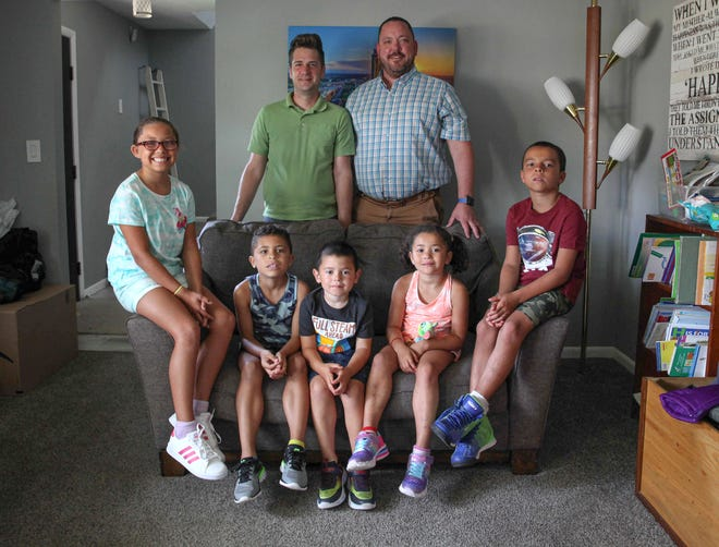 Chris and David Friest are shown with their five children, from left, Jordin, 9, Parker, 7, Turner, 5, Jaida, 5, and Junior, 7, in the living room of their Beaverdale home on Tuesday, Aug. 24, 2021, in Des Moines.