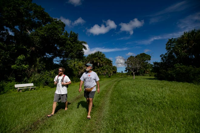 Tyler Martin, left, and Ed Gregoire hike along the Calusa Heritage Trail, an almost 1-mile interpretive walkway that leads visitors through the mounds, canals, and other features of the Pineland archaeological site.