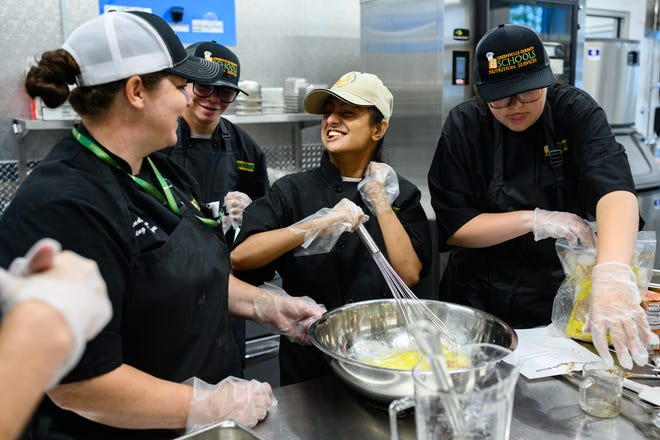 Barsha Parajuli, middle, whisks an apple pie mix that she and other special needs students are learning to make as part of a Greenville County Schools culinary training program at the Roper Mountain Science Center kitchen Friday, Aug. 20, 2021.