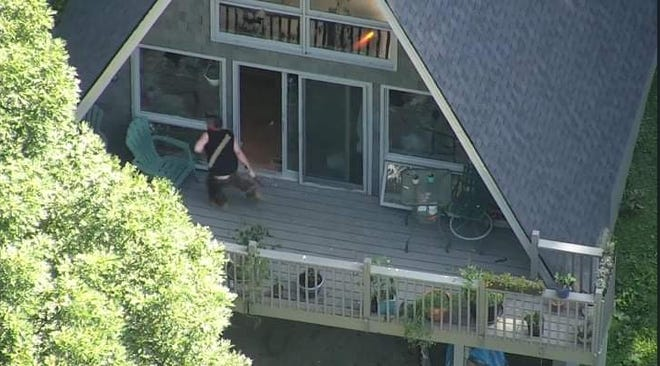 A flash, apparently from a weapon, is seen coming from the upstairs window as Sean Rowe runs on the deck of his home. It was unclear in this photo whether officers had fired a non-lethal round or an actual bullet.
