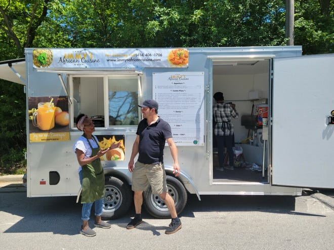 Immy Kaggwa talks with Pedro Tejada, who helped customize the food trailer for Immy's African Cuisine.