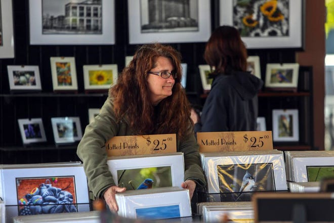 Among the market's artisans is Wright by Design of Brighton, which specializes in photos of Michigan locales, especially Farmington. Suzette Wright, above, and husband Ron have been part of the market for more than 15 years.