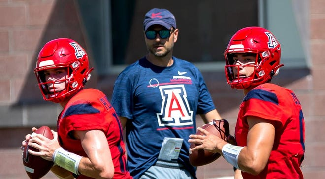 Arizona quarterbacks Will Plummer, 15, left, and Gunner Cruz, 9, look to through the ball down field during a drill at football practice at Dick Tomey Practice Fields in Tucson, Ariz. on August 13th, 2021.